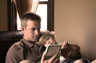 c father reading book to daughte